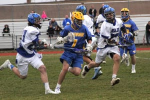 Comsewogue's Trevor Kennedy squeezes between two Hauppauge players in a match on April 7. Photo by Desirée Keegan