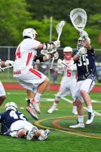 Smithtown East's John Daniggelis shoots the ball while Smithtown West's Zach Lamberti hoists his stick up to defend in the Division I semifinal game on May 22 where East topped it crosstown rival 17-11. Photo by Bill Landon