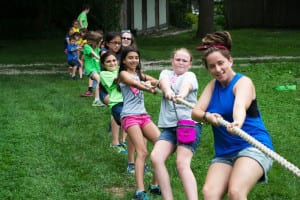 Camp counselors and young campers yank on a rope in a tug-of-war exhibition at Benner's Farm. Photo by Michaela Pawluk