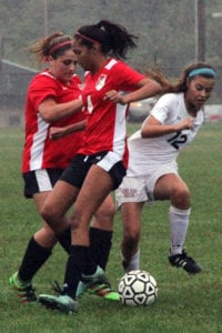 Samantha Hogan redirects the ball around East Islip defenders. Photo by Desirée Keegan